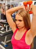 Sport girl in red holding dumbbells into sport gym. Biceps foreground. Royalty Free Stock Images