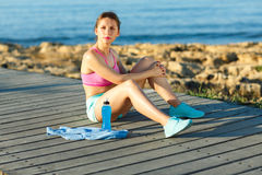 Sport girl resting after jogging on a wooden path at the sea Stock Photography
