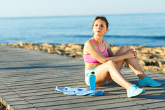 Sport girl resting after jogging on a wooden path at the sea Royalty Free Stock Photography