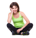 Sport girl sitting on the floor with her legs crossed and resting Stock Photos