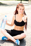 Sport girl sitting with thumb up, holding water Stock Photo