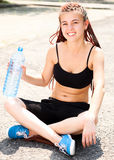 Sport girl sitting with water Stock Photography