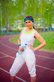 Sport girl on stadium with water bottle. Pretty sport girl standing on running track in forest holding water bottle outdoor Royalty Free Stock Image