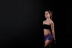 Sport girl stands and looks aside on black background. Stock Photo