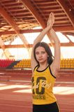 Sport girl in track and field athletics playpen. Sport girl in yellow suit pose in track and field athletics playpen stock photography