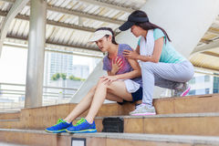 Sport girl try to help her friend who having symptomatic chest pain. Myocardial infarction Stock Image