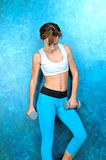 Sport girl in wear for fitness stands near blue wall Royalty Free Stock Photos