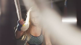 Sport girl working out with ropes in the dark gym. Slowly stock video footage
