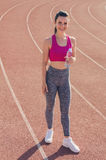 Sport girl workout. Exercise. Fitness. Health. Young  girl hold. Sport girl workout. Young  girl hold bottle of water at stadium do some training and looking at Stock Photography