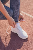 Sport girl workout. Exercise. Fitness. Health. Young girl tying. Sport girl workout. Young girl tying her shoelaces at stadium do some training. Exercise Stock Photo