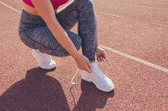 Sport girl workout. Exercise. Fitness. Health. Young girl tying. Sport girl workout. Young girl tying her shoelaces at stadium do some training. Exercise Stock Photography
