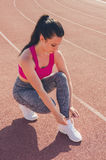 Sport girl workout. Exercise. Fitness. Health. Young girl tying. Sport girl workout. Young girl tying her shoelaces at stadium do some training. Exercise Stock Image