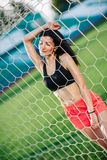 Sport girls in shorts and black top posed near football goal. young woman do sport exercises in sport wear. stock photography