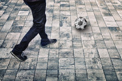 Sport grunge city person legs with soccer ball. Grunge city person legs with soccer ball on city floor. Sport recreation concept background with man feet. Grunge Royalty Free Stock Image