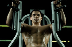 Sport guy. Very power athletic guy ,  execute exercise on  on sport-apparatus, in  sport-hall, beauty glamour light Royalty Free Stock Image