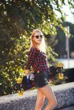 Sport happy girl posing in summer with skateboard. Stylish lucky hipster woman with colorful longboard in sunset in Royalty Free Stock Photo