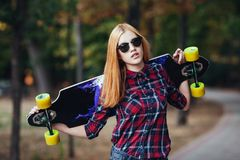 Sport happy girl posing in summer with skateboard. Stylish lucky hipster woman with colorful longboard in sunset in Stock Images