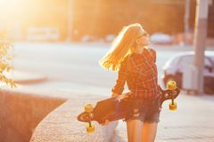 Sport happy girl posing in summer with skateboard. Stylish lucky hipster woman with colorful longboard in sunset in Stock Photos