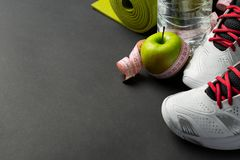 Different tools for sport and healthy food for diet on grey background. Sport, health and diet concept stock image