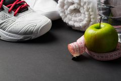 Sport shoes, measuring tape and water on grey background stock photography