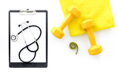 Sport and health. Fitness. Dumbbells and stethoscope on white background top view stock image