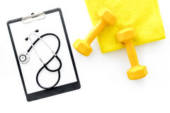 Sport and health. Fitness. Dumbbells and stethoscope on white background top view royalty free stock images