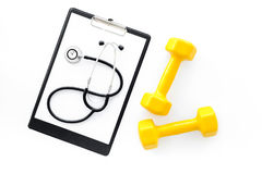Sport and health. Fitness. Dumbbells and stethoscope on white background top view Royalty Free Stock Photos
