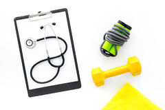 Sport and health. Fitness. Dumbbells and stethoscope on white background top view royalty free stock image