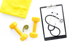 Sport and health. Fitness. Dumbbells and stethoscope on white background top view royalty free stock photography