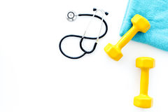 Sport and health. Fitness. Dumbbells and stethoscope on white background top view copyspace royalty free stock images