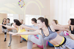 Sport and Healthlife Concepts. Group of Five Young Caucasian Females Making Stretching Exercises in Sport Class. Royalty Free Stock Images