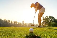 Sport Healthy. Golfer asian sporty woman focus putting golf ball on the green golf on sun set evening time. Healthy and Lifestyle Concept stock photography