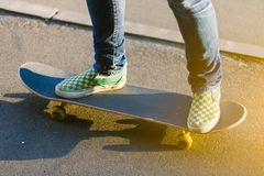 Skateboarder girl`s legs in sneakers doing a trick on skateboard outdoors. Sport and healthy lifestyle concept. Extreme trick on skateboard. Summer, outdoors stock photo