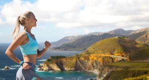 Woman with fitness tracker running outdoors. Sport and healthy lifestyle concept - smiling young woman with fitness tracker running over big sur hills and royalty free stock photos