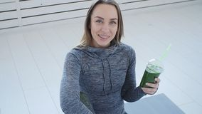 Sport and healthy lifestyle concept. Young woman with cup of smoothie at yoga studio or gym stock video footage