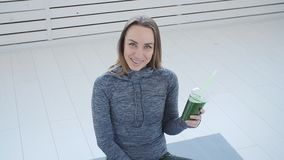 Sport and healthy lifestyle concept. Young woman with cup of smoothie at yoga studio or gym. Sport and healthy lifestyle concept. Young happy woman with cup of stock video footage