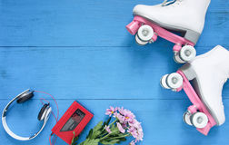 Sport, healthy lifestyle, roller skating background. White roller skates, headphones and vintage tape player. Flat lay Royalty Free Stock Image