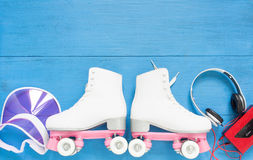 Sport, healthy lifestyle, roller skating background. White roller skates, retro headphones and pink visor hat. Flat lay, top view. Stock Photo