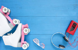 Sport, healthy lifestyle, roller skating background. White roller skates, sunglasses, headpfones and vintage tape player. Flat lay Royalty Free Stock Image
