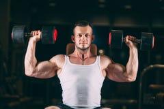 Sport, het bodybuilding, gewichtheffen, levensstijl en mensenconcept - jonge mens die met domoren spieren in gymnastiek buigen royalty-vrije stock fotografie