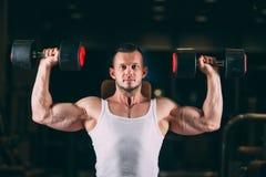 Sport, het bodybuilding, gewichtheffen, levensstijl en mensenconcept - jonge mens die met domoren spieren in gymnastiek buigen stock foto