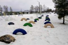 Sport, Hindernislauf auf dem Schulhof im Freien, mehrfarbige LKW-Räder nett Winter, lizenzfreie stockfotos