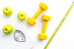 Sport i dieta dla gubić ciężar Łazienki skala, jabłko i dumbbell na białego tła odgórnym widoku, zdjęcia royalty free