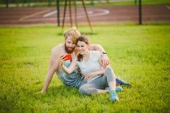 Sport i technologia Potomstwa w miłości heteroseksualnej Kaukaskiej parze odpoczywa w parku na gazonie po tym jak trening outdoor zdjęcia stock