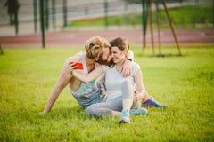 Sport i technologia Potomstwa w miłości heteroseksualnej Kaukaskiej parze odpoczywa w parku na gazonie po tym jak trening outdoor zdjęcie royalty free