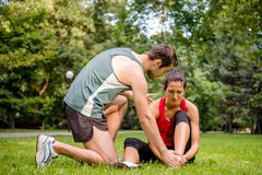 Sport injury - helping hand. Sport injury - young fitness women holding her ankle  with pain, men is helping Stock Image