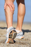 Sport injury - Man running clutching calf muscle. Muscle injury - Man running clutching his calf muscle after spraining it while out jogging on the beach. Male Royalty Free Stock Images