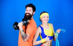 Sport instructor. Healthy lifestyle concept. Man and woman exercising with dumbbell and jumping rope. Fitness exercises royalty free stock photo