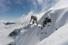 Sport invernali estremi Lo Snowboarder che salta in montagne nevose Immagine Stock Libera da Diritti