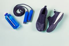 Sport items. Jumping rope, sport shoes, blue bottle with water. Items arranged on light green background. Photo with copy blank space royalty free stock image